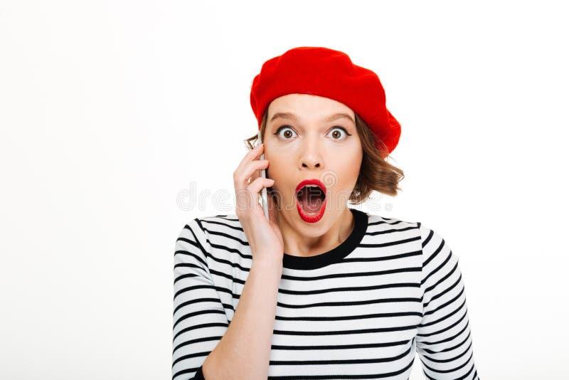 Jonge geschokte vrouw die door mobiele telefoon spreken stock afbeelding