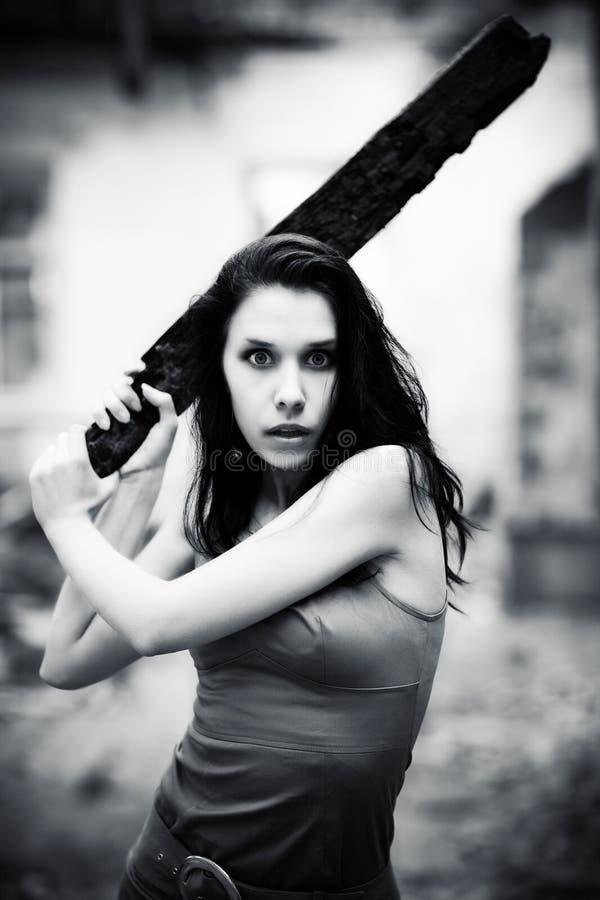 Jonge gevaarsvrouw met stok stock foto's
