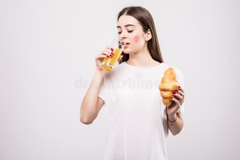 Jonge gezonde die vrouw met glas sap en cakes op witte achtergrond wordt geïsoleerd Het concept van de gezondheid royalty-vrije stock foto