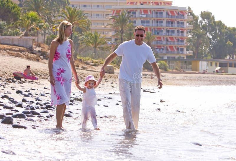 Jonge, gezonde familie die langs een zonnig strand lopen