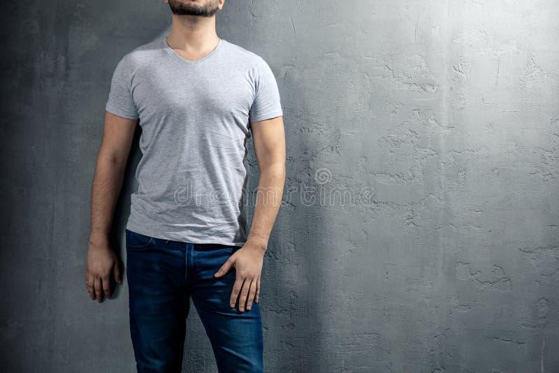 Jonge gezonde mens met grijze T-shirt op concrete achtergrond met copyspace voor uw tekst stock foto's