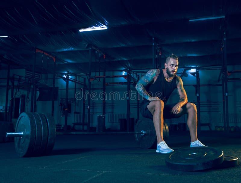 Jonge gezonde mensenatleet die voor opleiding in de gymnastiek voorbereidingen treffen stock afbeeldingen