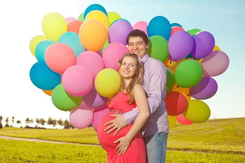 Jonge gezonde schoonheids zwangere vrouw met haar echtgenoot en ballon stock foto's