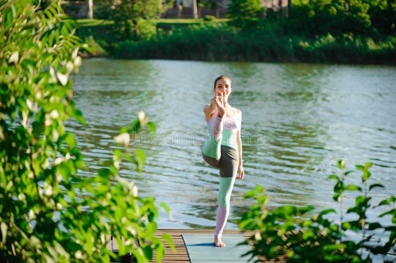Jonge gezonde vrouw het praktizeren yoga bij zonsondergang royalty-vrije stock foto's