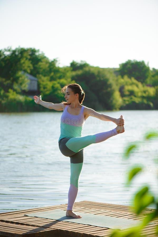 Jonge gezonde vrouw het praktizeren yoga bij zonsondergang royalty-vrije stock afbeeldingen