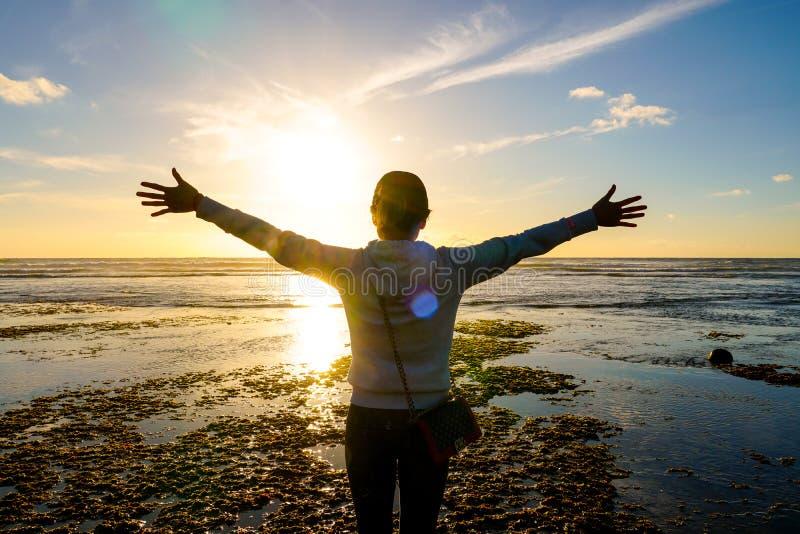 Jonge gezonde vrouw het praktizeren yoga op het strand bij zonsondergang stock foto's