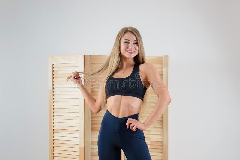 Jonge gezonde vrouw in sportkleding het stellen Gelukkig mooi meisje die bij camera glimlachen stock afbeelding