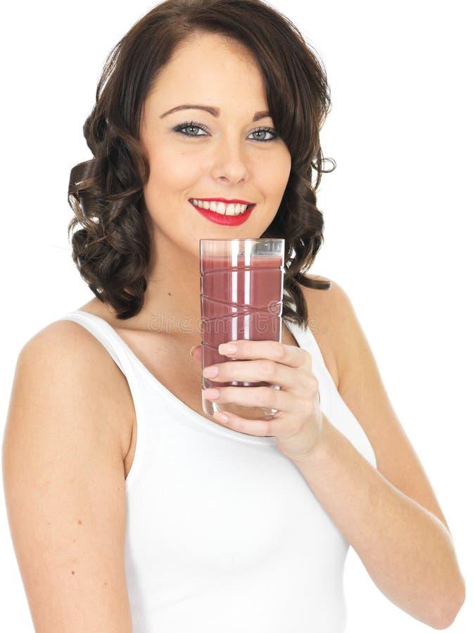 Jonge Gezonde Vrouwenholding die een Glas van Gemengd Berry Smoothie drinken stock afbeeldingen