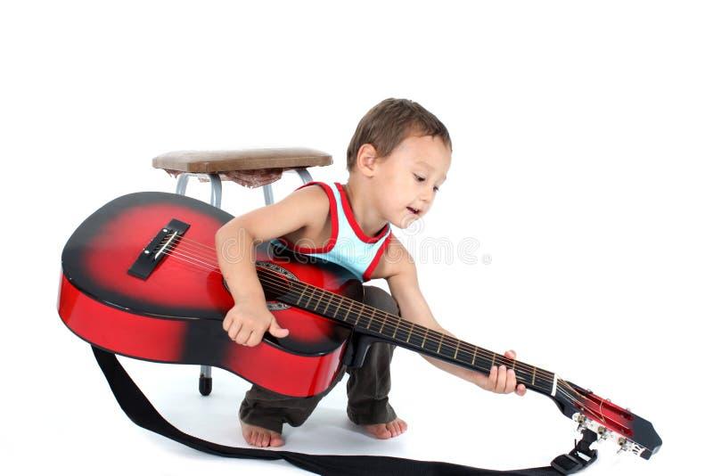 Jonge gitaarspeler 4 éénjarigen op een witte achtergrond stock afbeelding