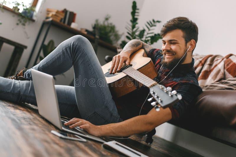Jonge gitarist die hipster thuis op de muziek van de gitaaroortelefoons van de vloerholding het doorbladeren laptop zitten stock foto