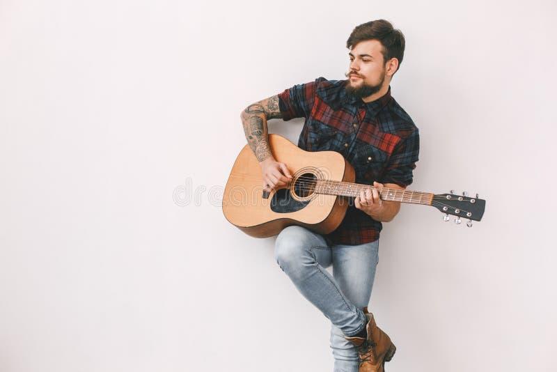 Jonge gitarist hipster thuis het spelen gitaar die het geïsoleerde glimlachen bevinden zich royalty-vrije stock foto
