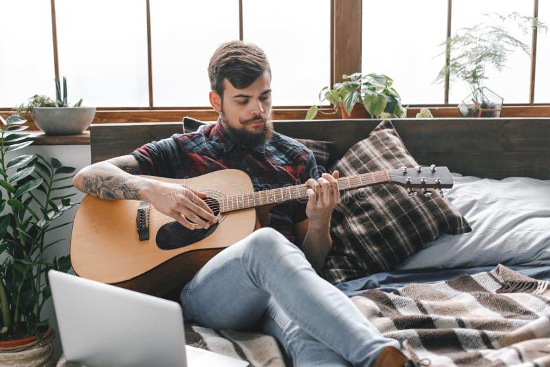 Jonge gitarist hipster thuis met gitaar in slaapkamer ernstig spelen stock foto's
