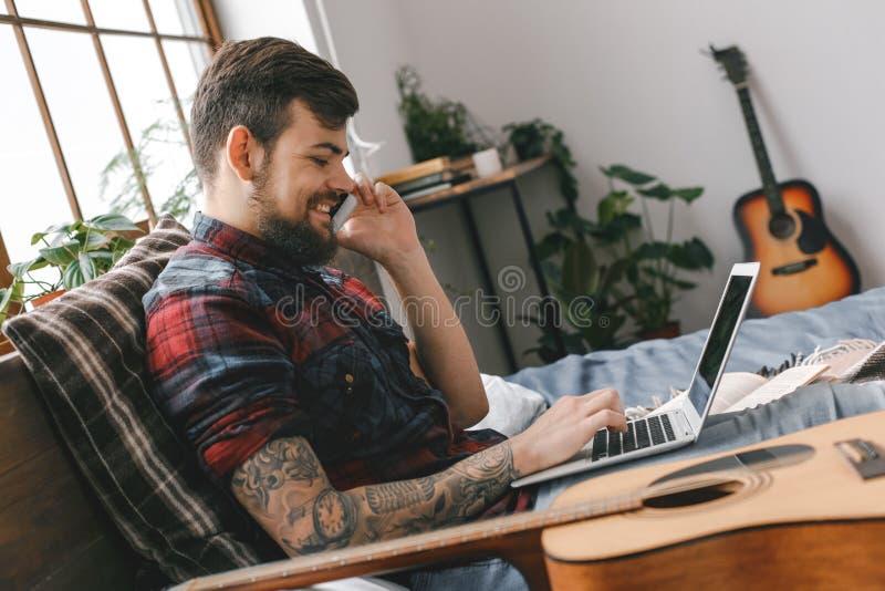 Jonge gitarist hipster thuis met gitaar in slaapkamertelefoongesprek royalty-vrije stock afbeeldingen