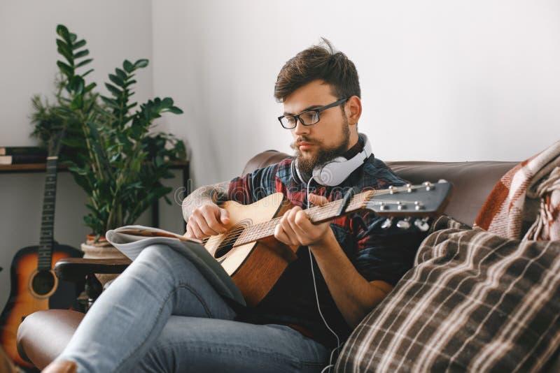 Jonge gitarist hipster thuis met gitaarzitting die oogglazen het spelen dragen stock foto