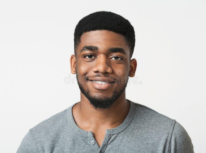 Jonge glimlachende Afrikaans-Amerikaanse mens over witte achtergrond royalty-vrije stock afbeeldingen