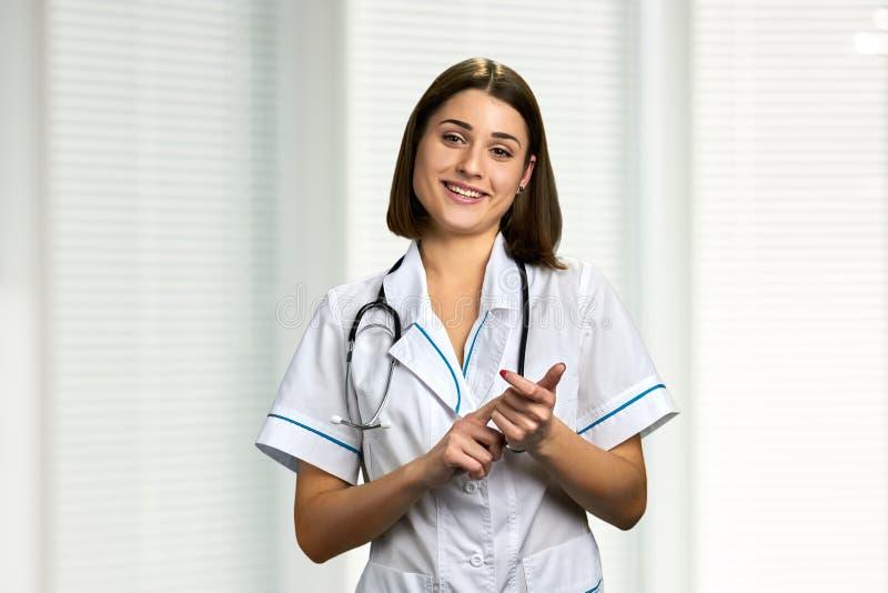 Jonge glimlachende arts die aan camera spreken stock foto's
