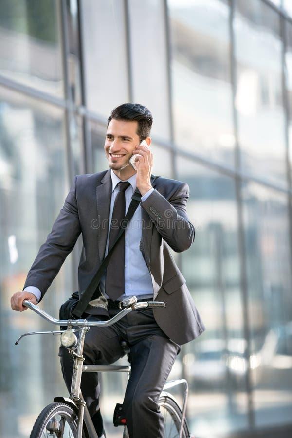 Jonge glimlachende bedrijfsmens met telefoon die een fiets berijden royalty-vrije stock fotografie