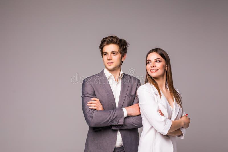 Jonge glimlachende bedrijfsvrouw en bedrijfsdieman op grijze achtergrond wordt geïsoleerd royalty-vrije stock afbeeldingen