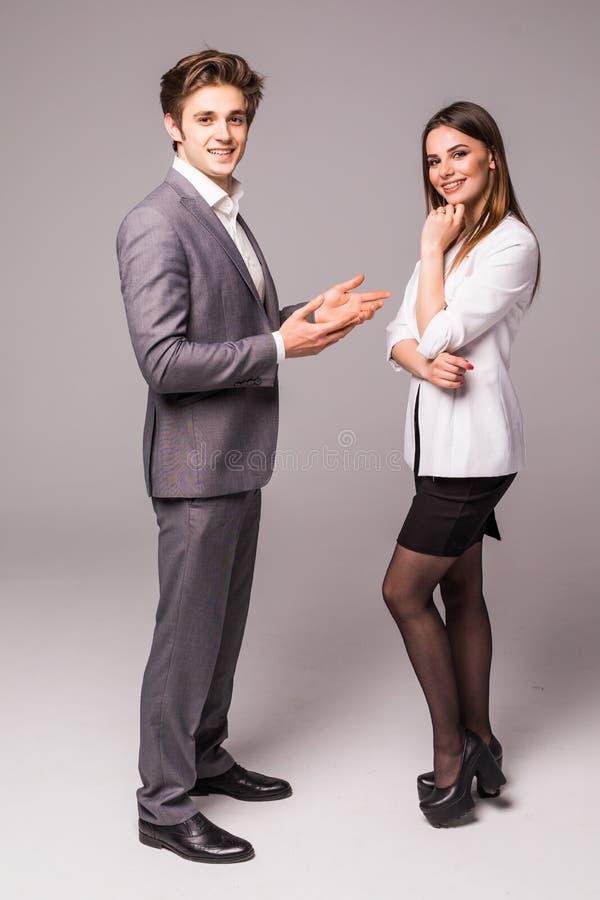 Jonge glimlachende bedrijfsvrouw en bedrijfsman op grijze achtergrond royalty-vrije stock afbeeldingen