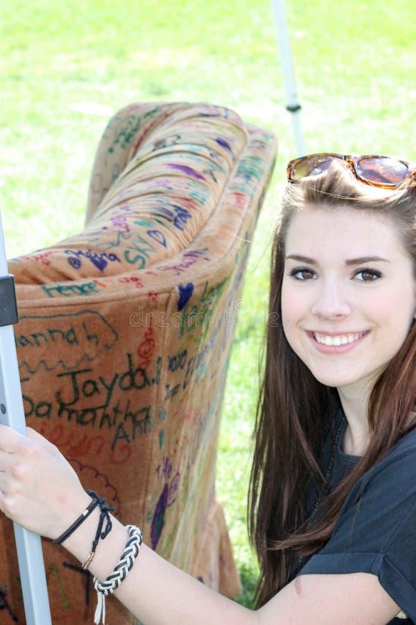 Jonge glimlachende dameholding op een laag royalty-vrije stock afbeelding
