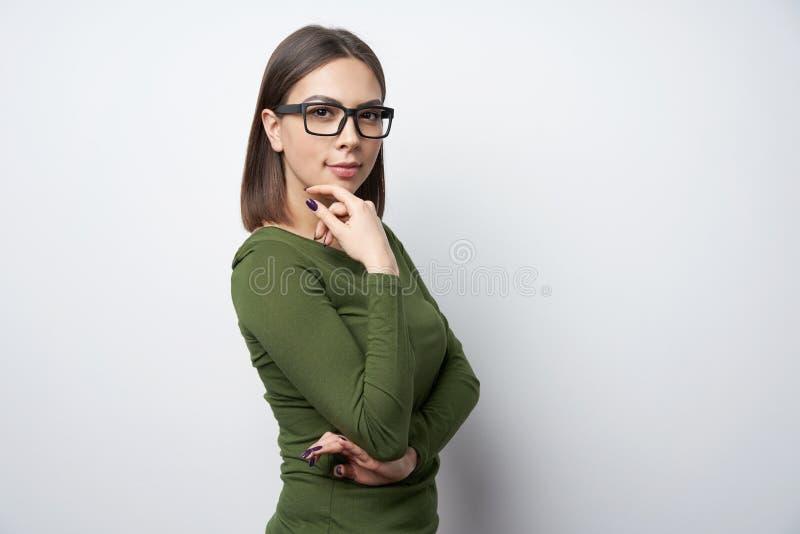 Jonge glimlachende donkerbruine vrouw die in glazen camera bekijken royalty-vrije stock foto's