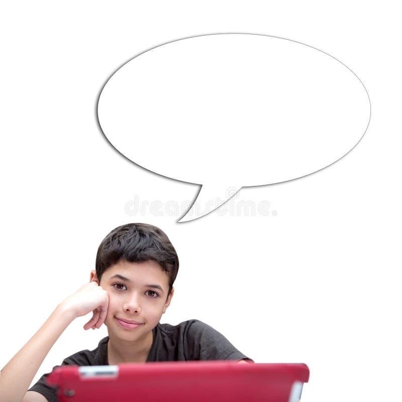 Jonge glimlachende jongen met één hand die op wang met toespraakbel tegen blauwe achtergrond rusten royalty-vrije stock afbeeldingen