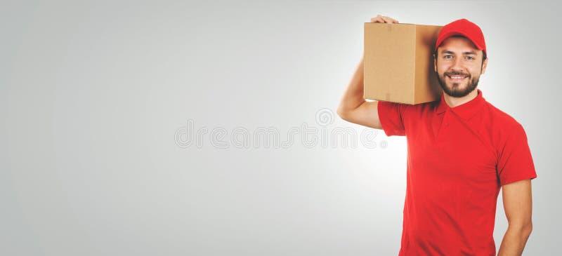jonge glimlachende leveringsmens in rode eenvormig en met verzendingsdoos op schouder royalty-vrije stock afbeeldingen