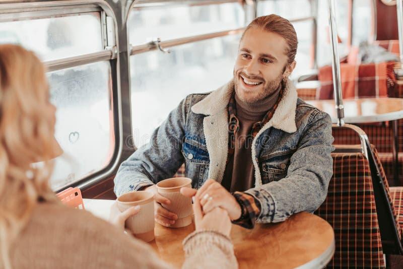 Jonge glimlachende man die aan geliefde vrouw kijken royalty-vrije stock afbeeldingen