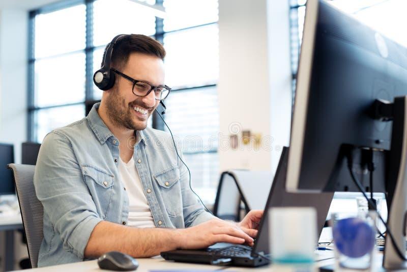 Jonge glimlachende mannelijke call centreexploitant die zijn werk met een hoofdtelefoon doen Portret van call centrearbeider op k royalty-vrije stock afbeeldingen