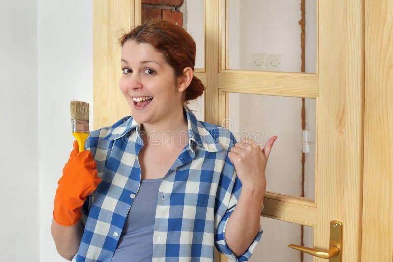 Jonge glimlachende meisjesarbeider, die nieuwe houten deur schilderen stock foto's