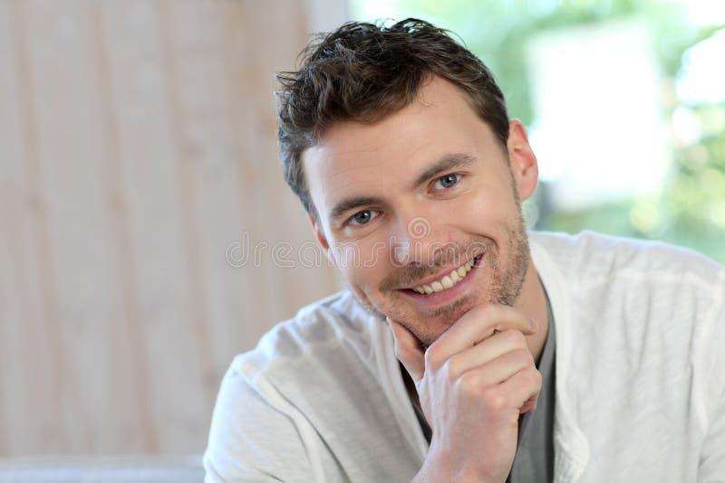 Jonge glimlachende mens thuis stock afbeelding