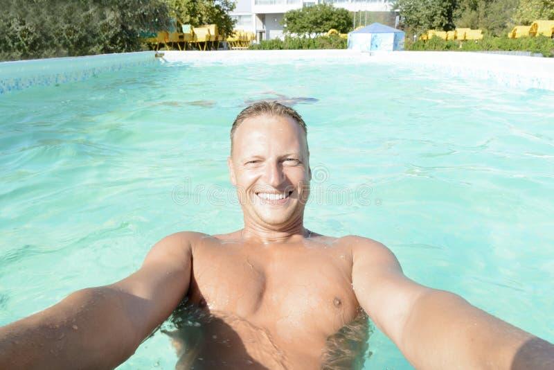 Jonge glimlachende mensenholding bij rand van zwembad royalty-vrije stock foto