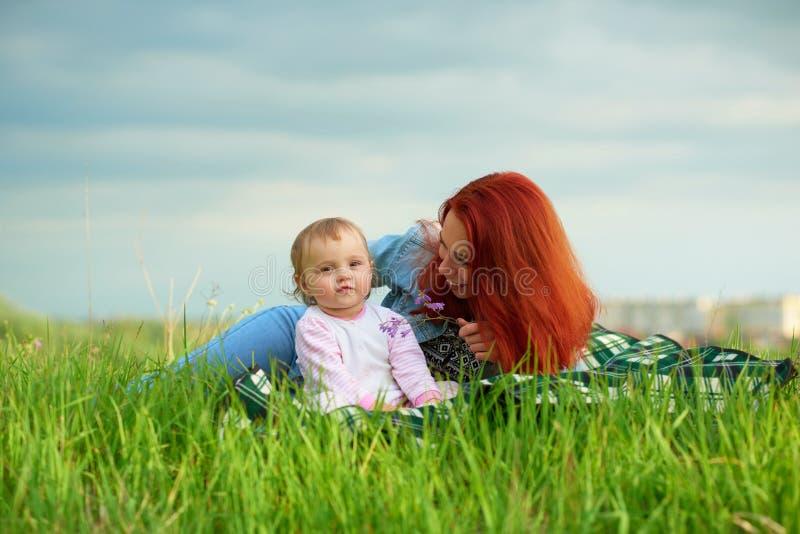 Jonge glimlachende moeder die met haar weinig dochter spelen die op gras leggen royalty-vrije stock fotografie