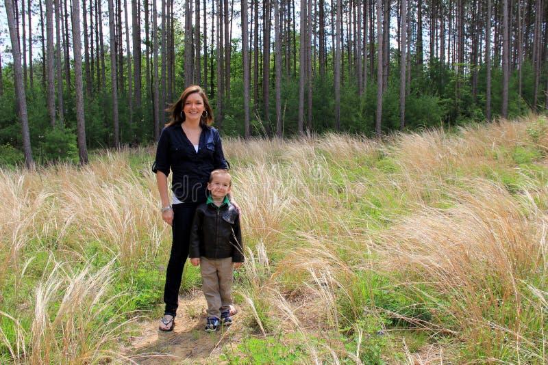 Jonge glimlachende moeder en zoon die zich in open grasrijke weide verenigen. stock foto's