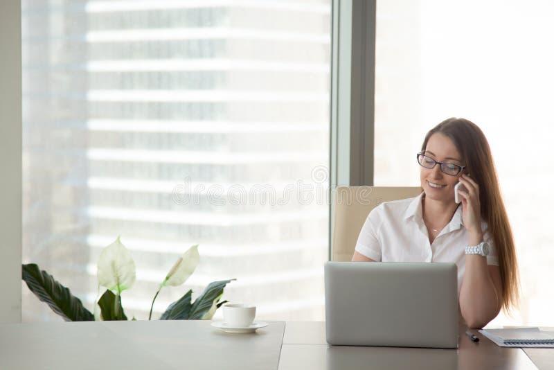 Jonge glimlachende onderneemster die op telefoon op het werk, mobil spreken stock foto's