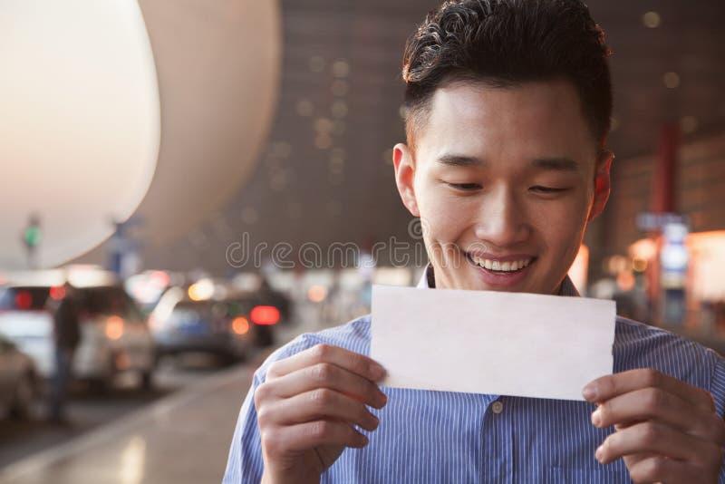 Jonge Glimlachende reiziger die kaartje bij luchthaven bekijken stock afbeeldingen