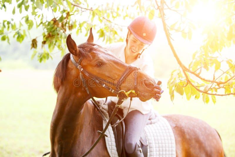 Jonge glimlachende ruitervrouw wat betreft lippen van paard stock fotografie