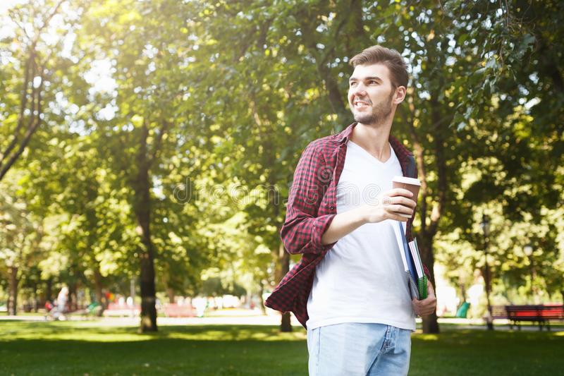 Jonge glimlachende student met koffie in openlucht stock afbeelding