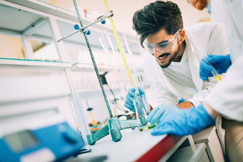 Jonge glimlachende student in witte laag die chemische taken doen royalty-vrije stock afbeelding