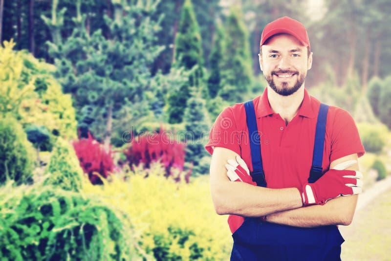 Jonge glimlachende tuinman met gekruiste wapens die zich in tuin bevinden royalty-vrije stock fotografie