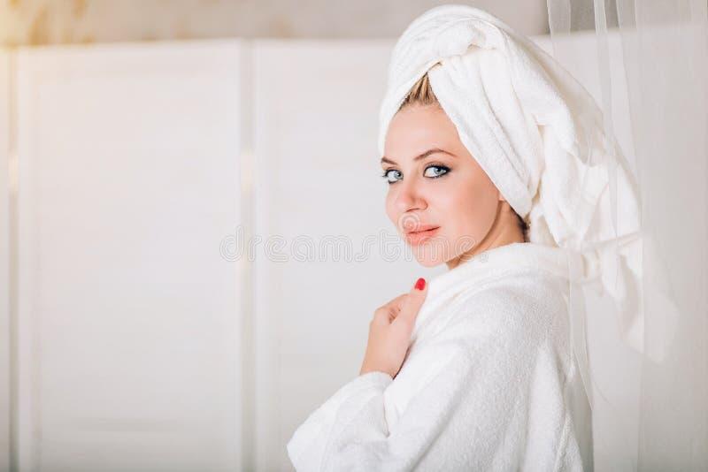 Jonge glimlachende vrouw in badjas met handdoek op hoofd stock afbeeldingen
