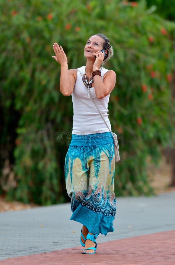 Jonge glimlachende vrouw die cellphone gebruikt stock afbeelding