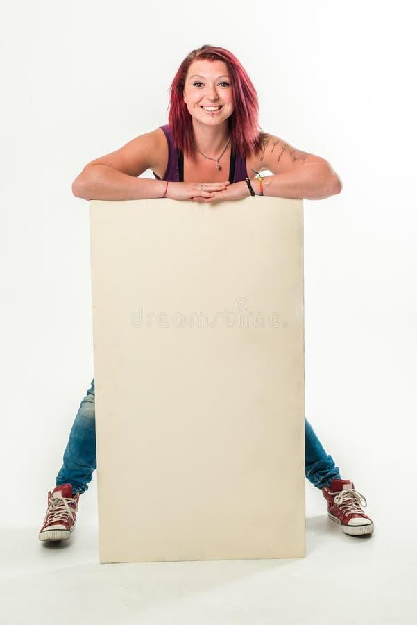 Jonge glimlachende vrouw die een lege witte banner houden royalty-vrije stock foto's