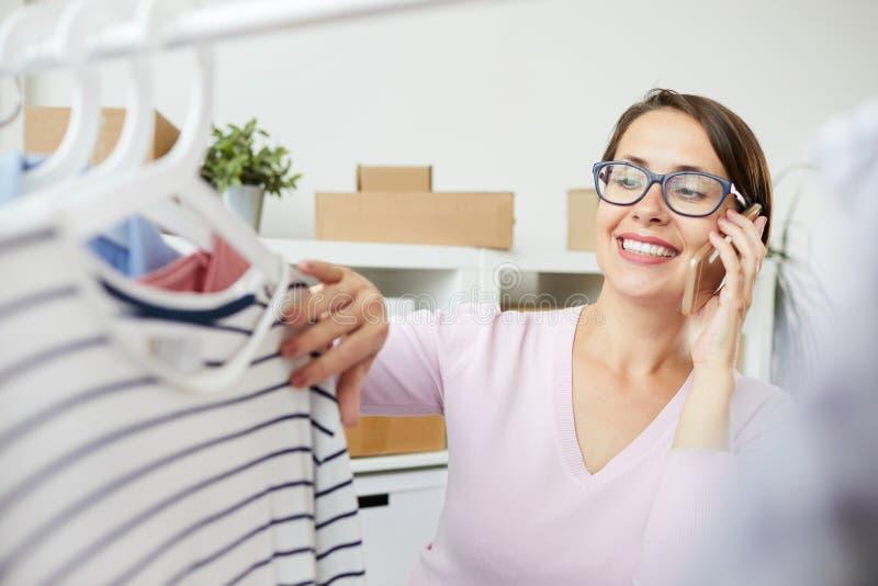 Jonge glimlachende vrouw die gestreepte trui op hanger bekijken royalty-vrije stock foto