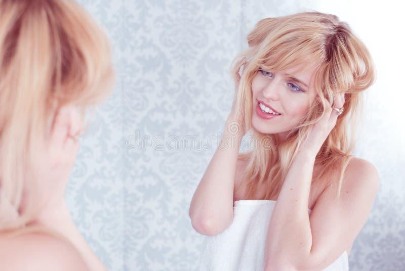 Jonge Glimlachende Vrouw die Haar in Spiegel verfomfaaien royalty-vrije stock afbeelding