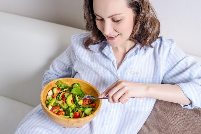 Jonge glimlachende vrouw die met blauw overhemd verse groentesalade eten royalty-vrije stock afbeeldingen