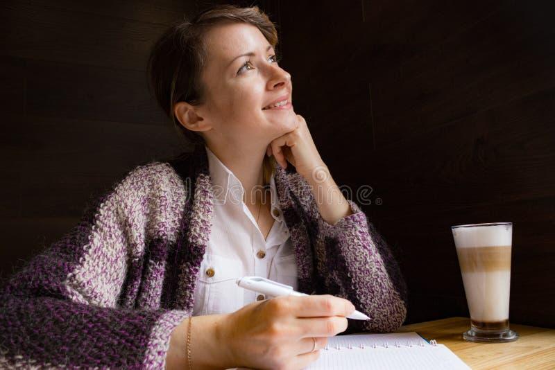 Jonge glimlachende vrouw die met pen en open notitieboekje denken Nadenkend meisjesportret Journalist en schrijversconcept Lifest stock fotografie