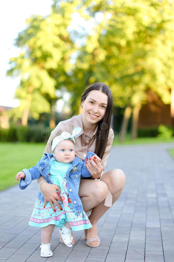 Jonge glimlachende vrouw die met weinig dochter in park lopen royalty-vrije stock afbeelding