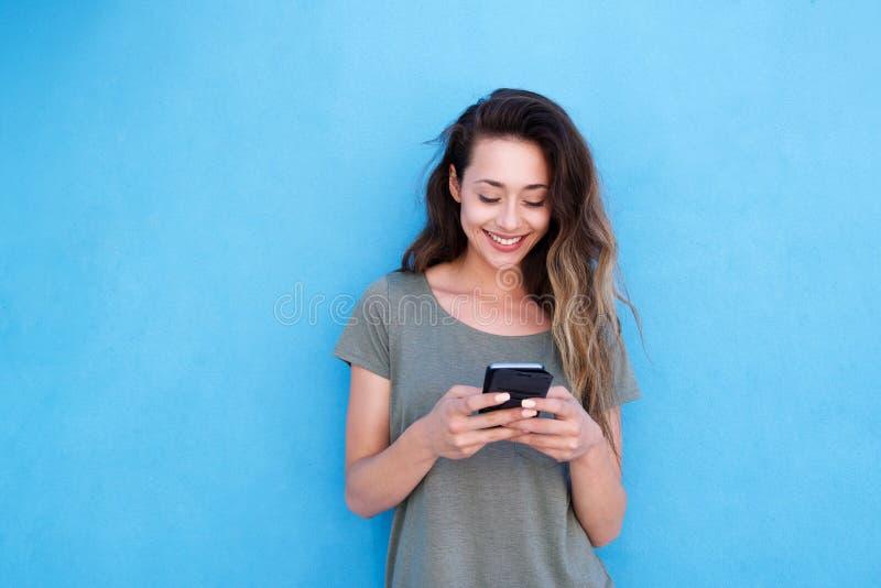 Jonge glimlachende vrouw die mobiele telefoon met behulp van tegen blauwe achtergrond royalty-vrije stock foto
