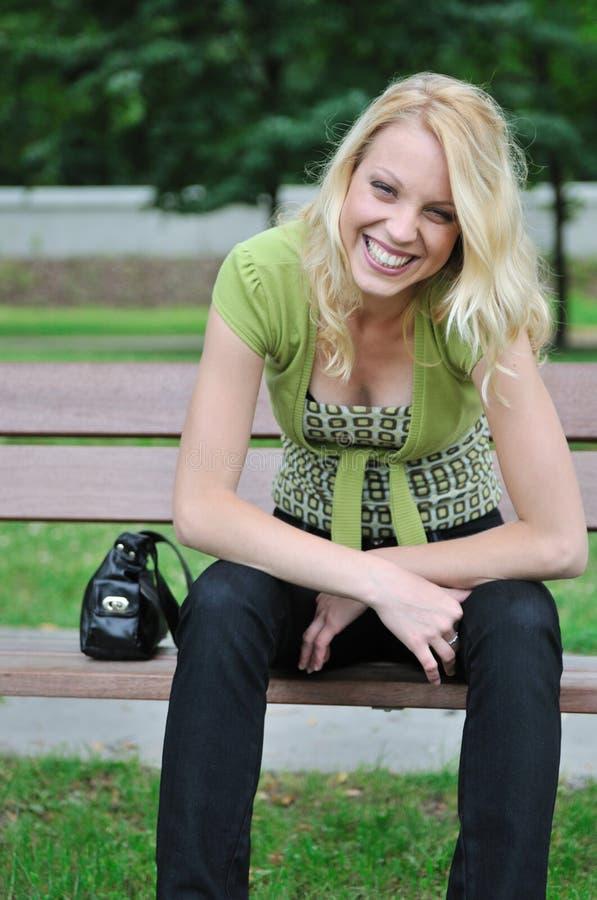 Jonge glimlachende vrouw die op bank in openlucht situeert royalty-vrije stock foto's